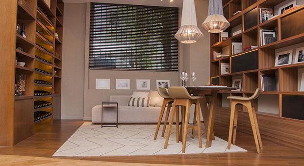 """WINE ROOM"""" de la Arq. Judith Babour (medalla de oro).  Cálido ambiente bodega, biblioteca, sofá y una mesa alta."""